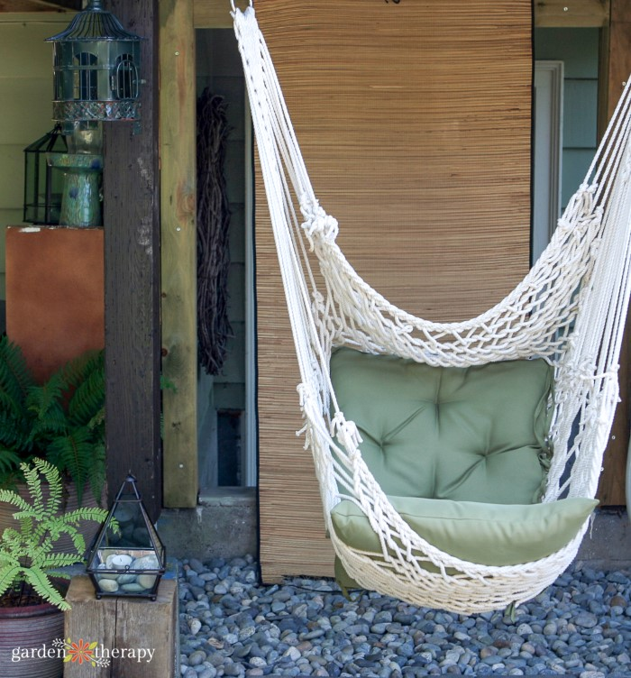 White macrame hammock chair with a green pillow in a backyard