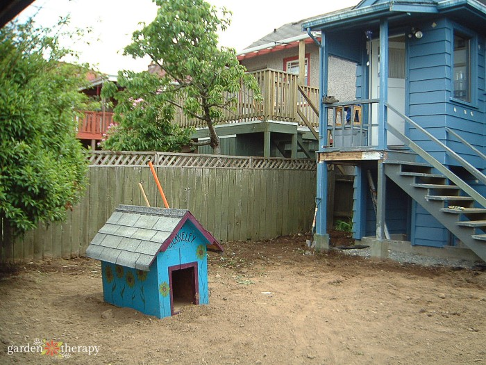 Fenced in backyard covered in dirt with a blue doghouse.