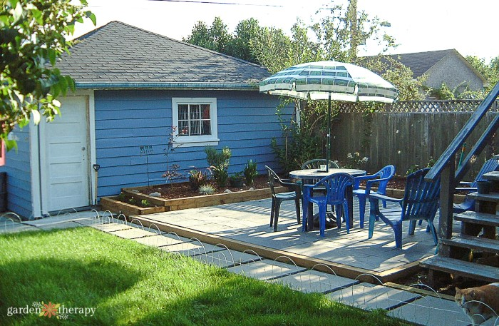 Blue home with a paved patio in the backyard