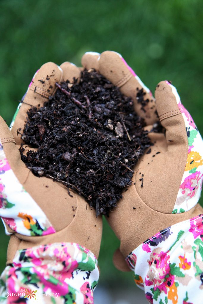 Woman holding handful of dirt during gardening for depression