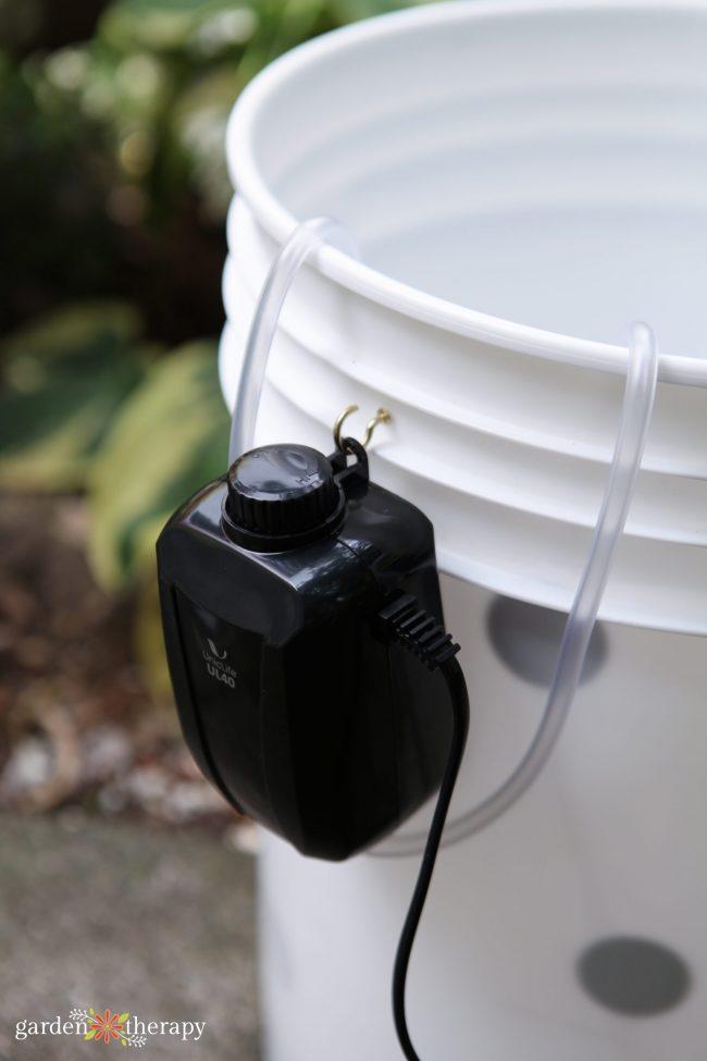 Aquarium air pump attached to a white 5 gallon bucket, creating a diy aerated tea brewer.