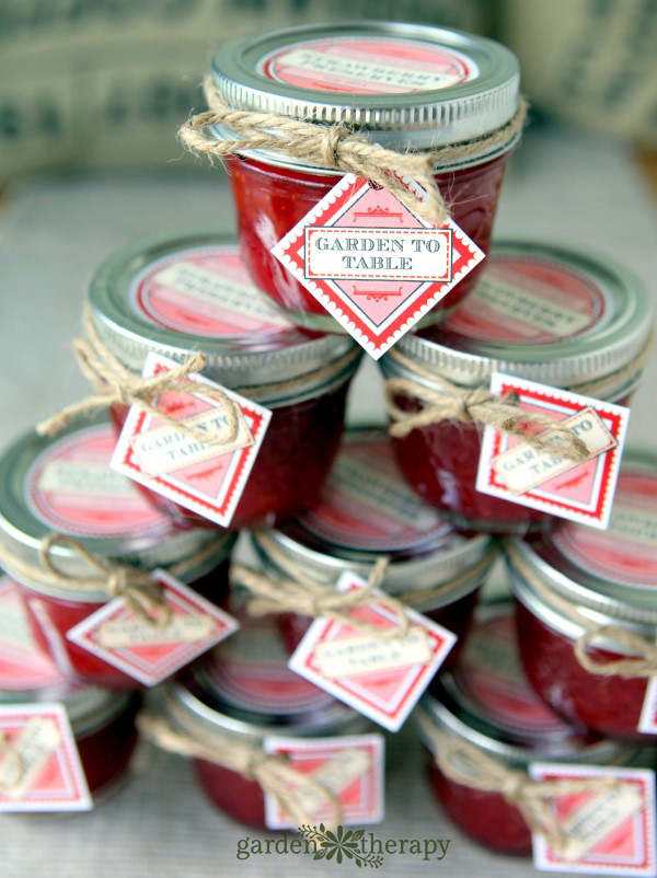 stack of homemade low sugar starwberry freezer jam with labels.