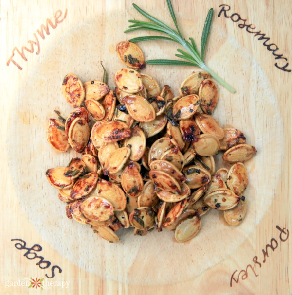 "roasted pumpkin seeds with a sprig of rosemary and lettering around the edges reading ""thyme, rosemary, parsley, sage"""