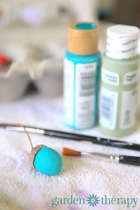 painting clay acorns from the DIY ornaments for the holidays tutorial