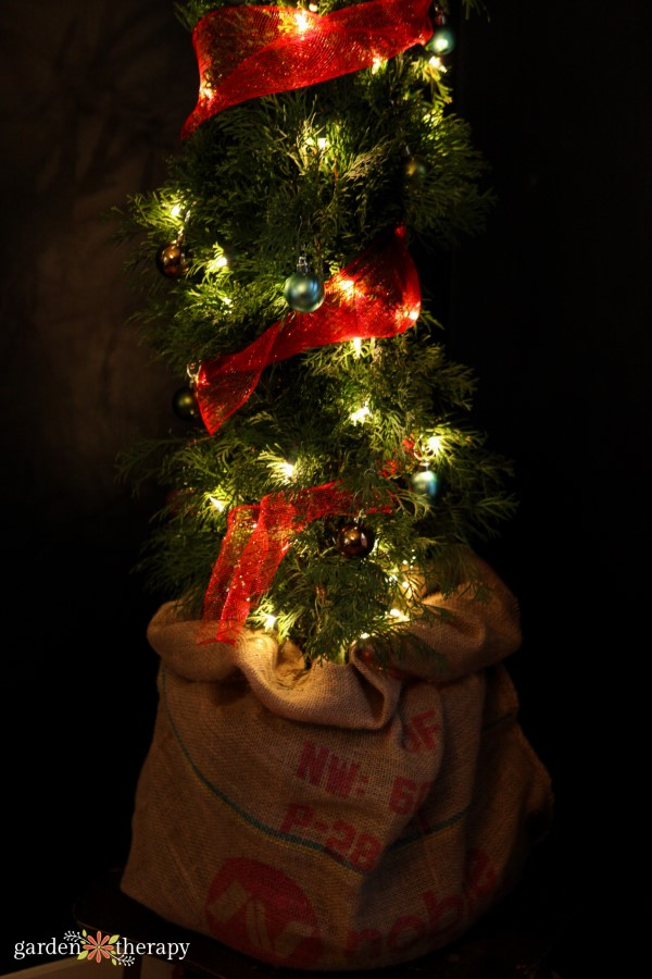 Grinch tree in a burlap sack with red mesh
