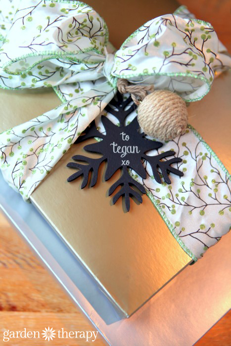 Gifts wrapped with chalkboad painted wood ornaments as gift tags