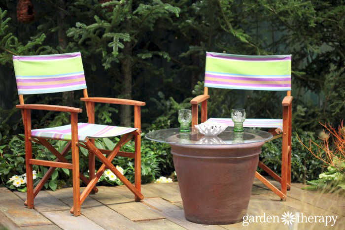 Outdoor table made from a large pot and a glass top from the Blue Greenhouse Seaside Garden Design Feature