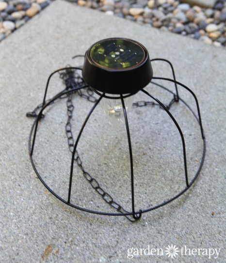 DIY Solar Light Chandelier sitting on a gray paver