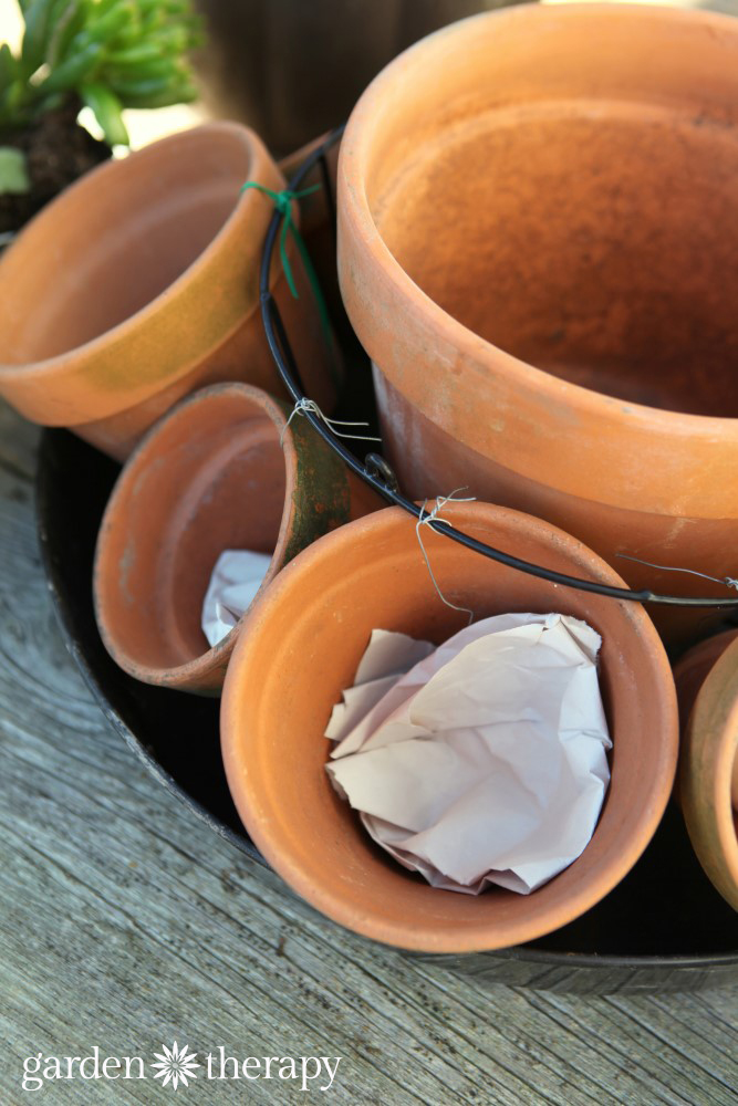 Adding paper to the bottom of pots to prevent soil drainage