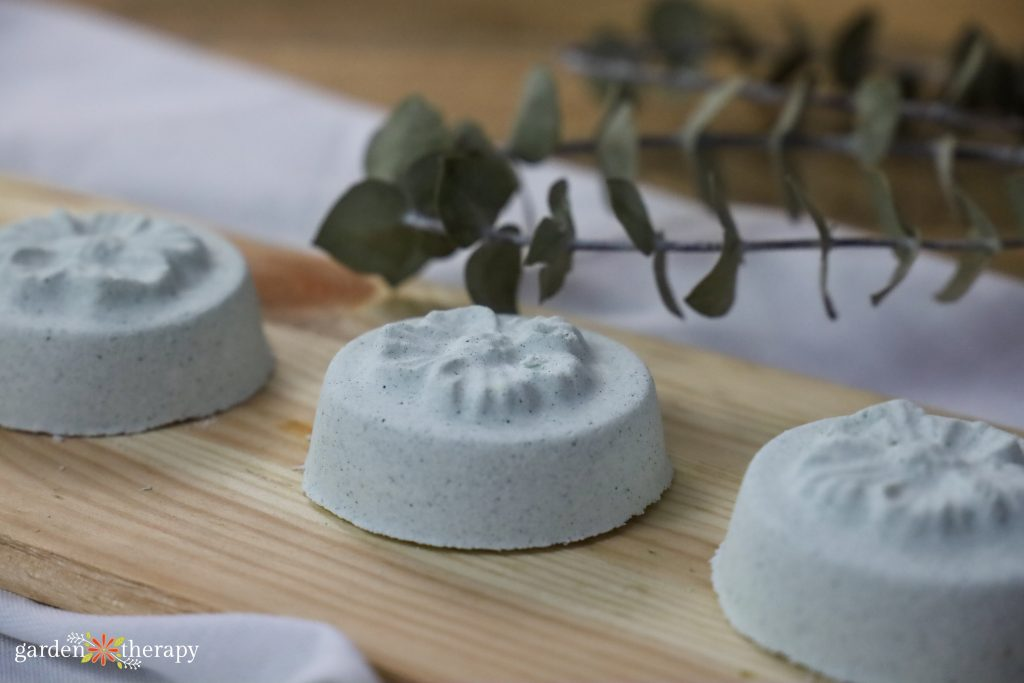 Flower-shaped shower steamers with eucalyptus leaves in background.