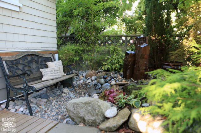 A secret garden space with a river stone and basalt disappearing fountain
