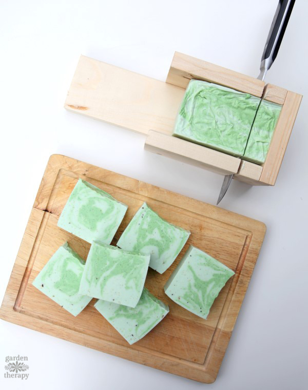 cutting a swirly green and white cedarwood soap mould onto a cutting board