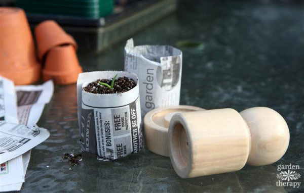Handmade newspaper seedling pots and a wooden pot-maker tool