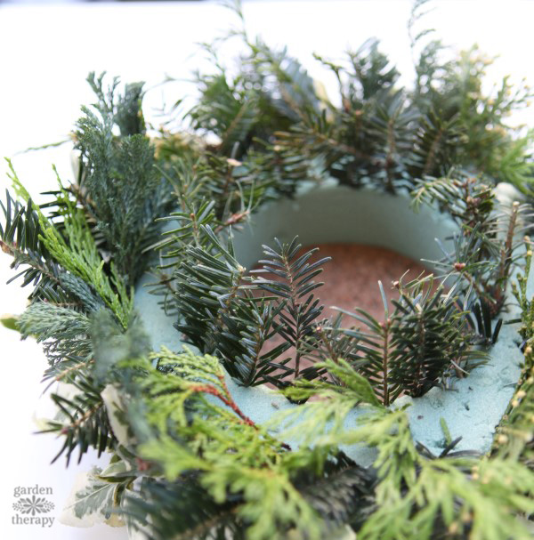 A festive DIY Christmas centerpiece with greenery and pinecones from the backyard