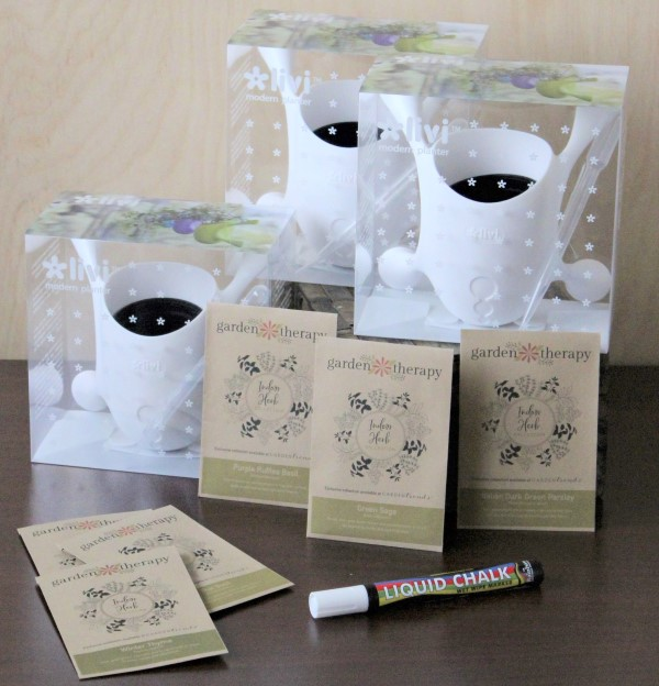A liquid chalk pen, six seed packets, and three white plastic pots with suction feet.