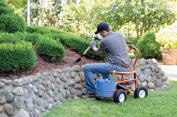 Man digging in the garden while seated in a wheeled garden seat