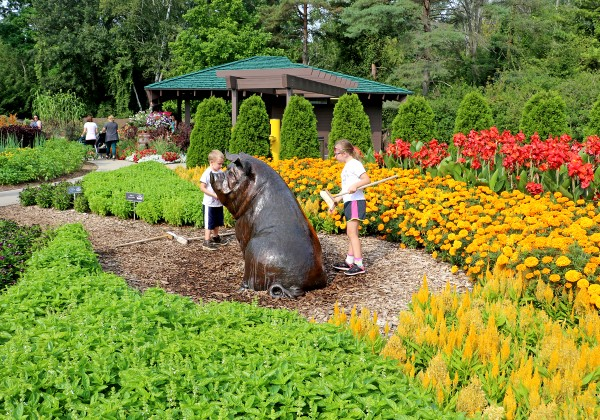 A large sculpture of a pig with two children standing beside it in the center of a garden