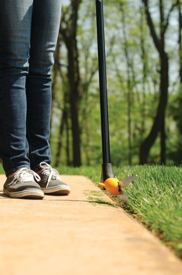 close-up image of a person's lower half wearing jeans and sneakers and using long-handled shears to cut grass along a walkway