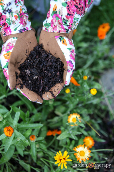 Woman holding custom garden soil in her cupped hands over flower bed.