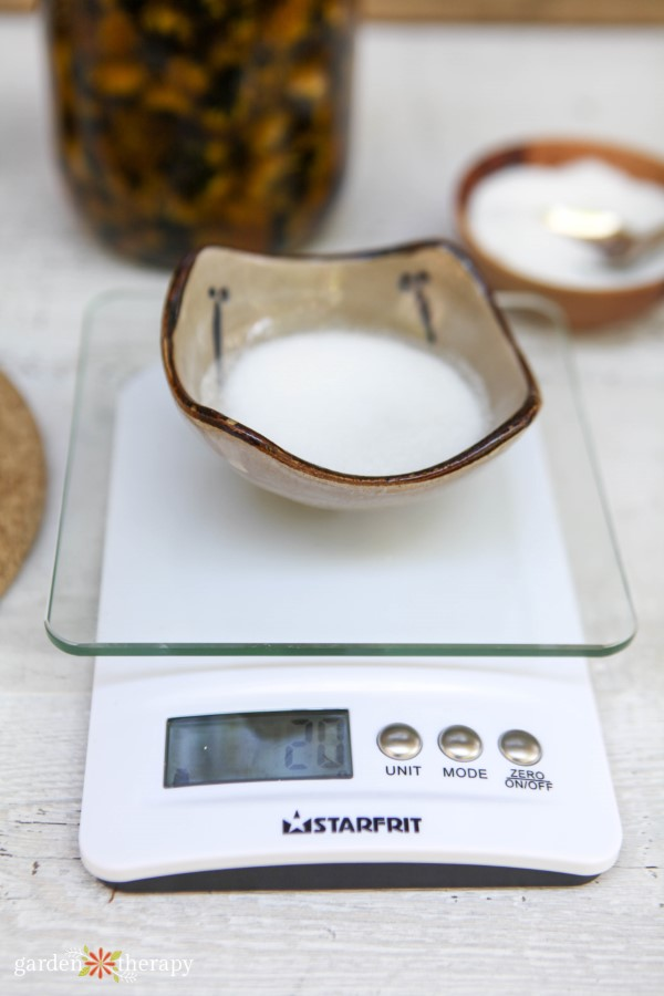 weighing sugar for an exfoliating lip scrub