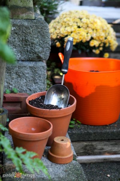Terracotta pots, one filled with soil and a hand trowel, and an orange bucket full of soil in front of a pot of yellow mums