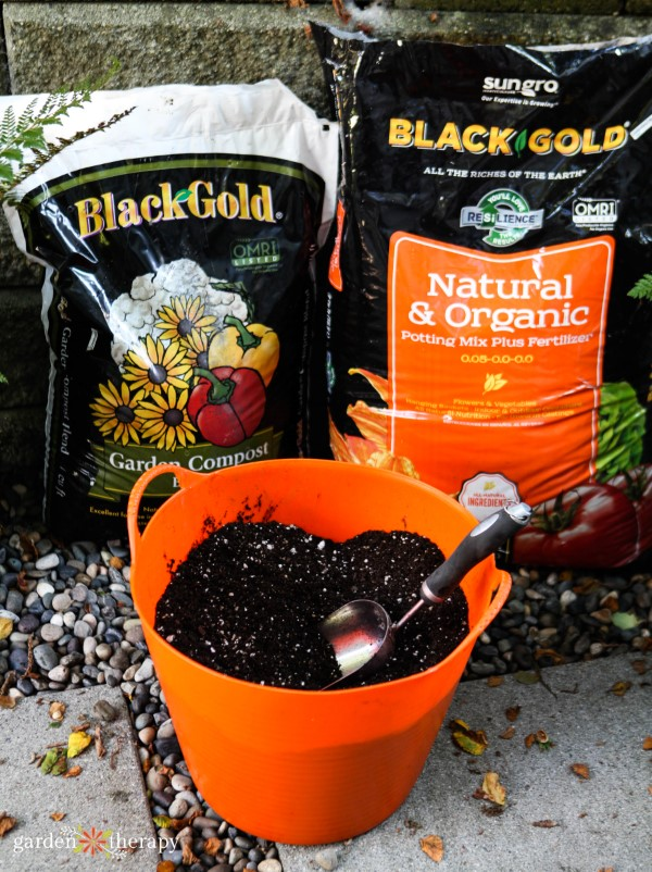 containers of black gold potting mix with an orange bucket for fall