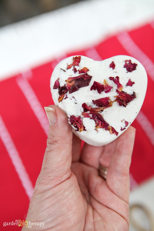 Woman holding a heart-shaped bath bomb with dried rose petals inside.