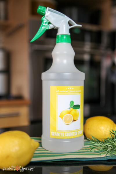 DIY granite cleaner with lemon and rosemary on a countertop