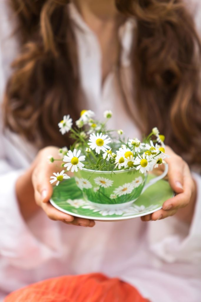 Woman holding a bowl of chamomile flowers