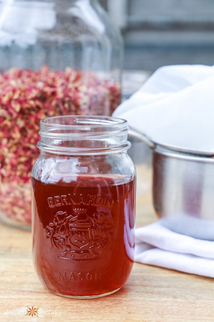 rose water in a mason jar in front of a pot and a jar of dried rose petals
