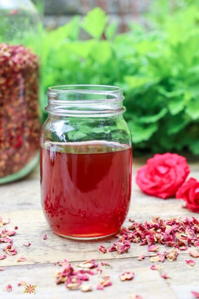 rose water in a mason jar with dried rose petals in another jar and on the table