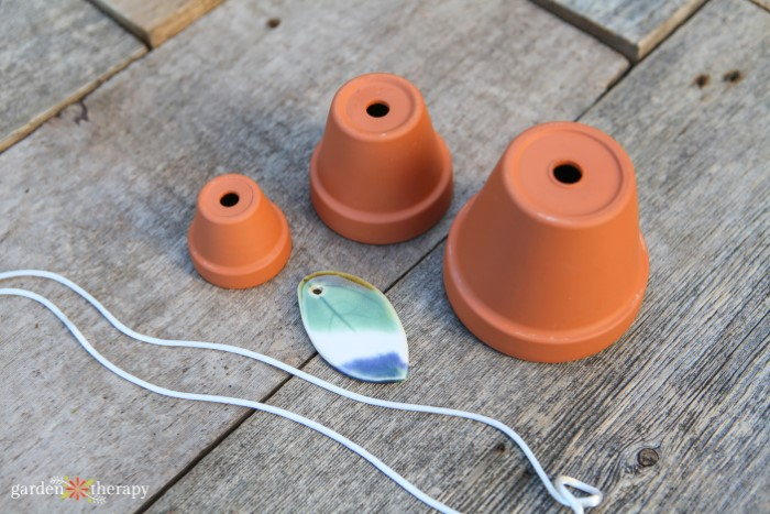 three terracotta pots, outdoor cord, and stone pendant