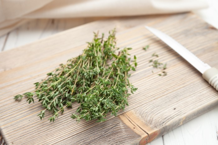 fresh thyme on a wooden cutting board