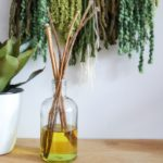 DIY reed diffuser in front of a textured art piece