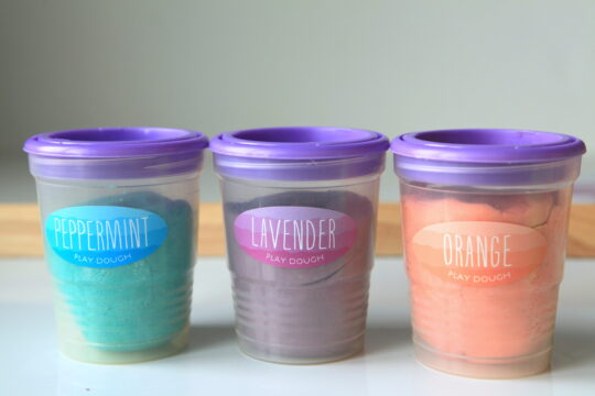 Labeled containers filled with scented playdough