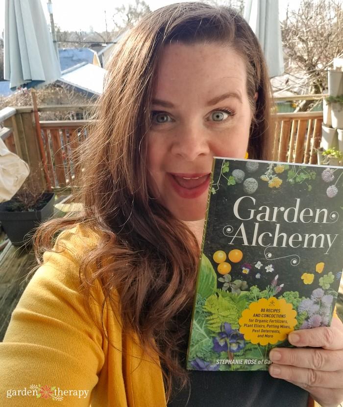 Author Stephanie Rose holding her book, Garden Alchemy