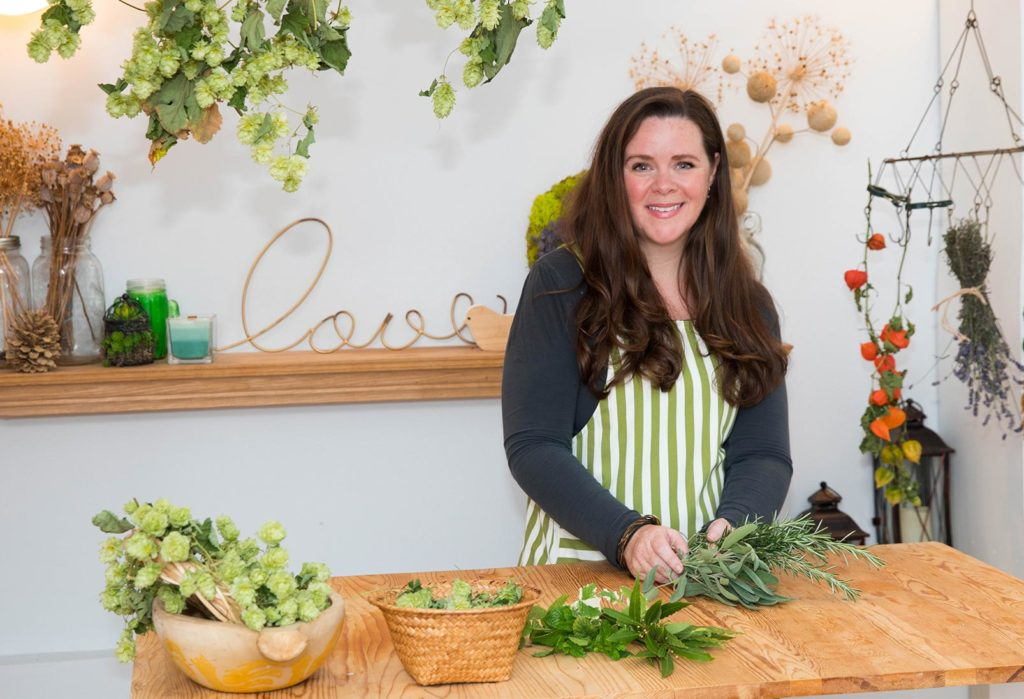 Stephanie standing at a table with bundles of herbs